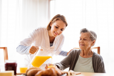 caregiver assisting the senior woman in her meal