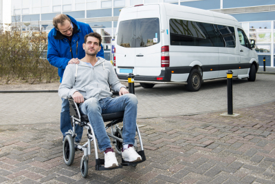 adult sitting in wheelchair with staff